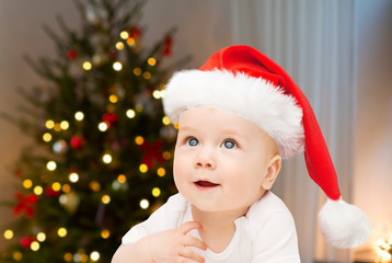 holidays, children and people concept - close up of happy little baby boy or girl in santa hat over christmas tree lights background