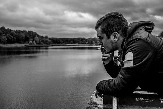 Задумчивый мужчина курит сигареты и смотрит в воду