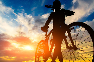 Silhouette of a cyclist on the background of a beautiful sky, view from below.