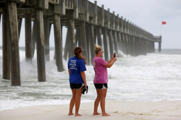 People take pictures of the ocean in advance of Hurricane Michael in Pensacola
