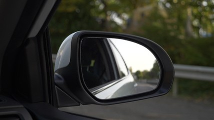 View out the rearview mirror, when the car passes along the road in the summer