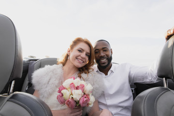 Portrait of smiling newlywed couple with bouquet sitting in convertible
