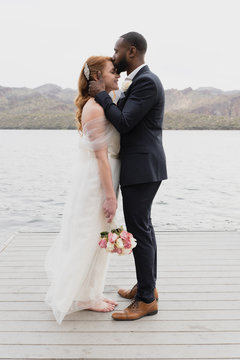 Husband kissing on wife's forehead while standing against lake