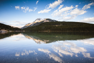 Scenic view of calm Lake Minnewanka by trees against blue sky at Banff National Park