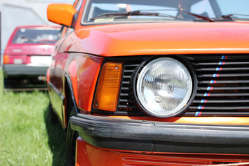 Exhibition of a retro cars. Big round headlight of a sports coupe bmw m3 e21.