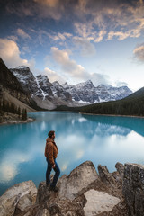 Side view of man looking at Moraine lake while standing on rock in Banff National Park during sunset