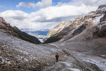 Rear view of hiker walking at Banff National Park against cloudy sky