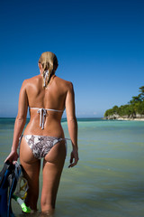 The backside of a blond woman in bikini walking in tropical waters with mask and fins after snorkelling