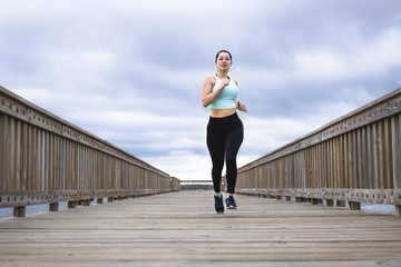 Low angle view of woman running on pier against cloudy sky