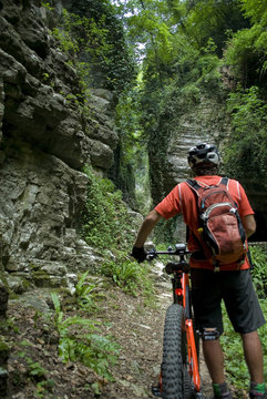 "man with an electric bike, e-bike, ebike, mtb, mountain, rock canyon created by a river, forest, summer, sport, adventure, freedom, alps, Path called ""Strada della Forra"", Garda Lake, Lombardy, Italy"