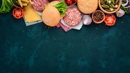 Preparation of burger. Meat, tomatoes, onions. On a black stone background. Top view. Free copy space.