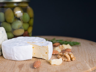 Variation of cheese, nuts and olives on a wooden platter