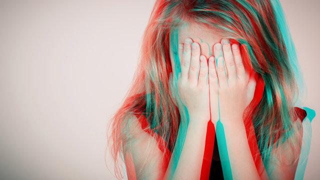 Portrait of sad blond little girl sitting near wall