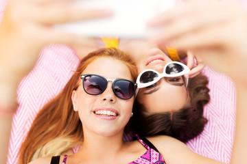 summer fashion, eyewear and leisure concept - smiling teenage girls in sunglasses lying on picnic blanket taking selfie