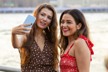 Two young women in New York taking a selfie photo with their smartphone