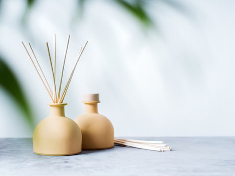 aroma reed diffuser home fragrance with rattan sticks on a light background with palm leaves and shadows.