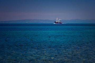 Fishing boat on the blue Aegean Sea in Samothrace Island in Greece with sea gulls surrounding it