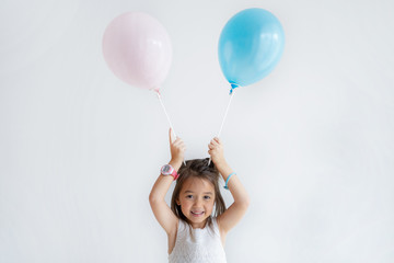 Happy little Caucasian girl holding balloons on top of her head and smiling. Pretty girl in princess outfit looking at camera. Birthday party concept.
