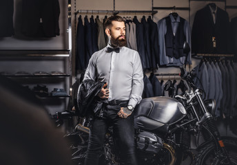 Elegantly dressed tattooed male with stylish beard holds black leather jacket posing near retro sports motorbike at the men's clothing store.