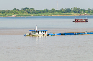 Cargo ship on the Mekong river in Cambodia, overloaded and low in the water