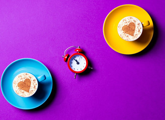 blue and yellow cups and clock on the purple background