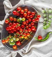 ripe red cherry tomatoes lie in a metal plate