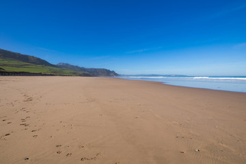 Landscape of beach named La Vega and Cantabrian Sea, with blue sky, in Ribadesella, Asturias, Spain, Europe