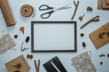 Black frame and christmas decoration top view. Christmas gift, scissors, notebook with pen, gift bags, pine cones, fir branches, acorns on wooden white blue background. Handmade mockup, invitation or
