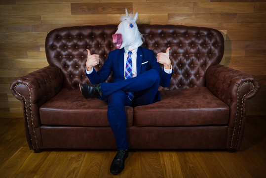 Funny unicorn in elegant suit sits on sofa like a boss and showing gesture thumbs up. Portrait of unusual man at home. Freaky guy in comical mask.