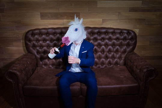 Funny unicorn in elegant suit sits on sofa with bottle of wine. Unusual man with headache at home. Freaky boss in comical mask on background of wooden wall.
