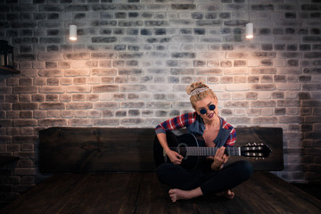 Glamour blonde girl in causal clothes playing music on guitar in stylish apartment. Unusual young woman sits on the bed at modern home.