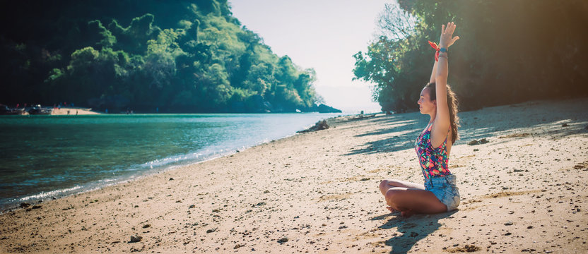 Fit woman relaxing and practicing yoga on the summer beach
