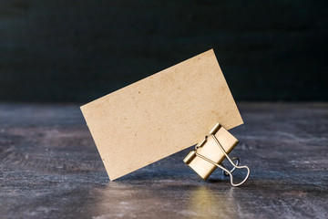 Business card from craft recycled paper with metal binder clip on table. Cardboard business card on dark background.