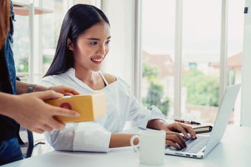 Business owner concept. Young two asian woman smiling happy using laptop working and checking customer product packaging for online order in modern home office