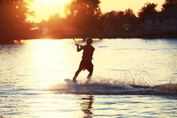 Wakeboarder surfing the lake on a warm summer evening