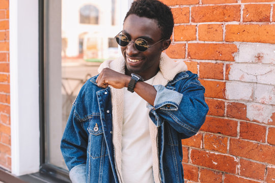 Fashion portrait smiling african man with smart watch using voice command recorder or takes calling on city street, brick wall background