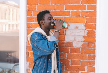 Break time! Happy smiling african man drinks coffee on city street, brick wall background, hipster walks