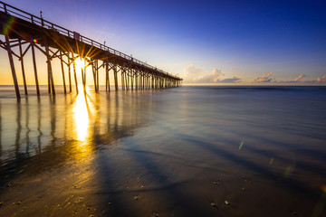 Sun shining on the horizon behind a pier during sunrise