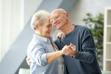 Cute elderly couple dancing at home
