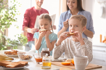 Little children having breakfast with toasts in kitchen