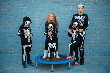 Cute children dressed up to celebrate Halloween in skeleton costumes jumping on trampoline. Boys and girl are happy together. Gym class on open space