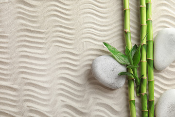 Bamboo branches with spa stones on sand, top view. Space for text