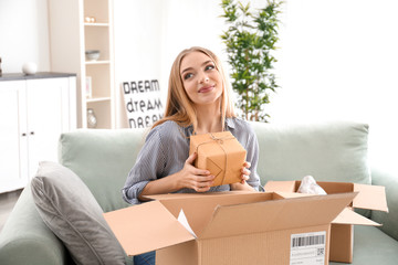 Young woman unpacking parcel at home