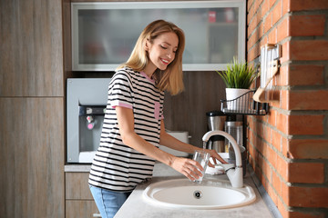 Young woman filling glass with water from faucet in kitchen