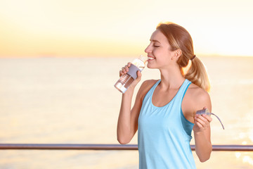 Young woman drinking water from bottle after fitness exercises on pier in morning