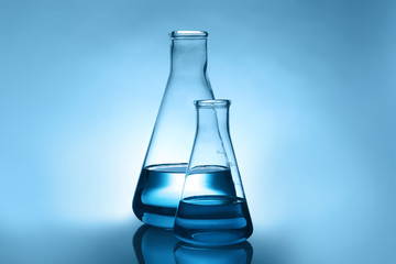 Conical flasks with liquid on table against color background. Laboratory analysis