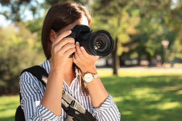 Young female photographer taking photo with professional camera in park. Space for text