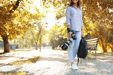 Young female photographer with professional camera and backpack in park. Space for text