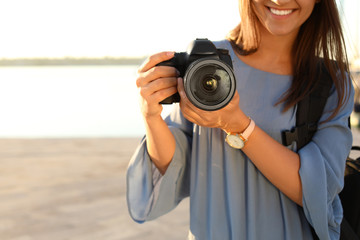 Young female photographer holding professional camera at pier, closeup. Space for text