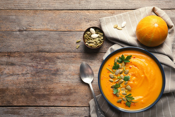 Tuinposter Aromatische Flat lay composition with pumpkin cream soup in bowl on wooden background. Space for text
